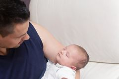 Neonato di Lovingly Holding His del padre strettamente fotografie stock