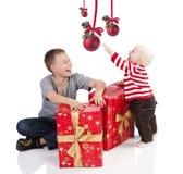 Neonato di natale con il contenitore di regalo con il fratello Fotografia Stock