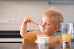 Neonato di un anno adorabile che mangia yogurt con il cucchiaio Fotografie Stock Libere da Diritti