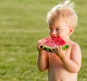 Neonato di un anno che mangia anguria nel giardino Immagini Stock