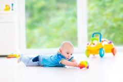 Neonato divertente che gioca con l'automobile variopinta del giocattolo e della palla Fotografia Stock