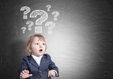 Neonato e punti interrogativi sulla lavagna Immagine Stock