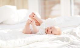 Neonato felice sul letto Immagini Stock