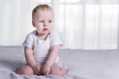 Neonato stanco e turbato Bambino infantile calmo che si siede sul letto attraverso dalla finestra Copi lo spazio Fotografia Stock Libera da Diritti