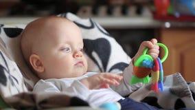 Neonato sul seggiolone con il giocattolo archivi video