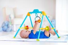 Neonato sulla stuoia del gioco Bambino che gioca nella palestra immagine stock