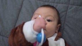 Neonato sveglio che gioca giocattolo Bambino sveglio che gioca con il crepitio sul letto video d archivio