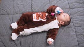 Neonato sveglio che gioca giocattolo Bambino sveglio che gioca con il crepitio sul letto stock footage