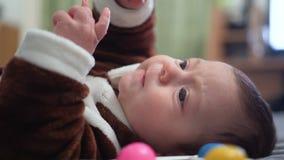 Neonato sveglio che gioca giocattolo Bambino sveglio che gioca con il crepitio sul letto archivi video