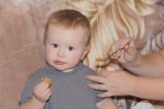 Neonato sveglio che mangia pane Fotografie Stock