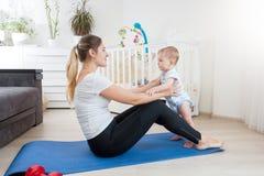 Neonato sveglio che si esercita con la giovane madre sulla stuoia di forma fisica a casa Fotografia Stock