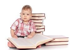 Neonato sveglio con molti libri isolati su bianco Fotografia Stock