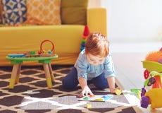 Neonato sveglio del bambino che gioca con i giocattoli sul tappeto a casa fotografie stock