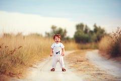 Neonato sveglio del bambino divertendosi gioco sul percorso al campo di estate Immagine Stock