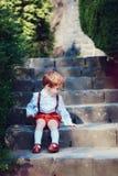 Neonato sveglio della testarossa che si siede sui trairs nel giardino di primavera fotografia stock libera da diritti