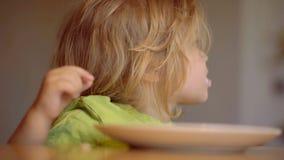 Neonato sveglio di risata del bambino che si siede in seggiolone e che mangia sul fondo della cucina Cibo affamato del ragazzino  video d archivio