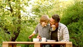 Neonato sveglio di risata del bambino che si siede in seggiolone e che mangia sul fondo verde della natura Ricevimento all'aperto stock footage