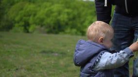 Neonato sveglio felice che gioca con il padre nel movimento lento del parco video d archivio