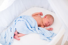 Neonato sveglio in letto bianco Immagini Stock