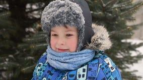 Neonato sveglio nei vestiti e nel portare di inverno un cappello contro lo sfondo di neve e di un albero di Natale stock footage