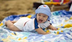 Neonato sveglio su un tovagliolo di spiaggia Immagini Stock