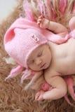Neonato tenero nell'allungamento rosa di sonni del cappuccio Immagini Stock