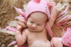 Neonato tenero nell'allungamento rosa di sonni del cappuccio Fotografie Stock Libere da Diritti