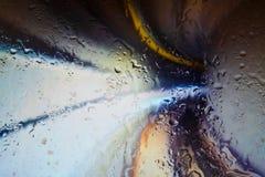 Neonlichter hinter Wassertropfen nah oben innerhalb der Tunnelgeschwindigkeitslichter stockfoto
