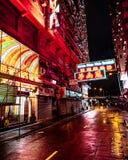 Neonljus i regniga Hong Kong gator på natten royaltyfri foto
