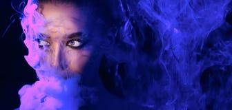neonpartij Vrouw het vaping in club, rook door neonlichten wordt verlicht dat stock foto