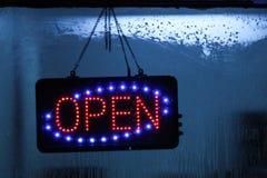 Neonteken Open op vensterwinkel stock foto