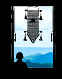 Neophyte at window (in partial silhouette) with thai  hanging mo. Bile in a public temple, Wat Pa Phu Kon,Thailand Royalty Free Stock Photo