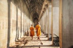 Two neophytes walking in an Angkor Wat, Siem Reap, Cambodia. The neophytes were walking inside an Angkor Wat in Siem Reap, Cambodia Stock Photos
