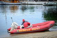 Two men in red rubber rescue boat checking boat on the bay stock image