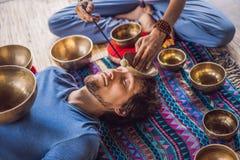 Nepal Buddhakopparsjunga bunke på brunnsortsalongen Ung härlig man som gör massageterapi som sjunger bunkar i Spa royaltyfri fotografi