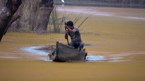 NEPAL - 11 DE NOVIEMBRE DE 2018: Pescador local Rowing Boat a través del lago almacen de metraje de vídeo