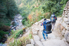 Nepal - 25 December 2016 :: Sherpas carry heavy backpack and wal Royalty Free Stock Photo