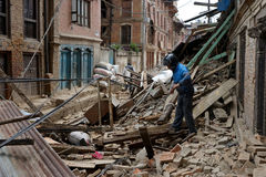 Nepal Earthquake 2015. MP014: A man makes his way through the debris of a residential building completely destroyed by the earthquake at Bhaktapur Durbar Square Stock Photo