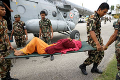 Nepal Earthquake 2015. MP058: Nepali Army medical personnel bring 25 April, 2015 earthquake victims from an Indian Air Force M17 Helicopter at Tribhuvan Royalty Free Stock Photos