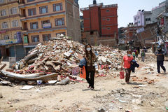 Nepal Earthquake 2015. MP073: People walk past a collapsed building destroyed during the April 25, 2015 earthquake in Gongabu area in Kathmandu, Nepal on May 1 Stock Image