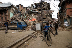 Nepal Earthquake 2015. MP020: People walk past a collapsed house completly destroyed by the earthquake at Bhaktapur Durbar Square, near Kathmandu, Nepal on April Stock Photo