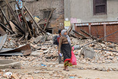 Nepal Earthquake 2015. MP032: A woman walks past a collapsed house completly destroyed by the earthquake at Bhaktapur Durbar Square, near Kathmandu, Nepal on Royalty Free Stock Photo