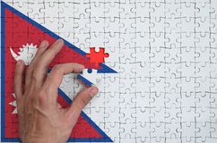 Nepal flag is depicted on a puzzle, which the man`s hand completes to fold.  royalty free illustration