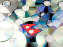 Nepal flag on top of CD and DVD pile isolated on white. Nepal flag on top of CD and DVD pile isolated Royalty Free Stock Photos