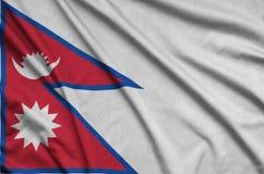 Nepal-Flagge wird auf einem Sportstoffgewebe mit vielen Falten dargestellt Sportteamfahne lizenzfreie stockfotos