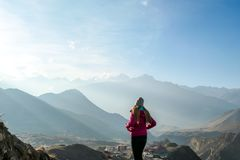 Nepal - A girl standing and admiring the view on tall Himalayas royalty free stock photography