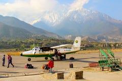 Nepal, Himalaja, Jomsom-Flughafen - April 2015: Touristen und lokale Leute flogen auf ein kleines Flugzeug zum Flughafen in den B Stockfotografie