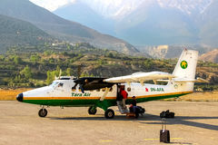 Nepal, Himalaja, Jomsom-Flughafen - April 2015: Touristen und lokale Leute flogen auf ein kleines Flugzeug zum Flughafen in den B Stockfoto