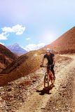 Nepal, Himalaya, el reino del mustango superior - abril de 2015: Un ciclista de la bici de montaña desciende el camino de la mont Foto de archivo libre de regalías
