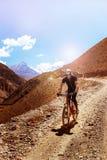 Nepal, Himalayagebergte, het koninkrijk van Hoger Mustang - April 2015: Een fietser van de bergfiets daalt de bergweg Royalty-vrije Stock Foto